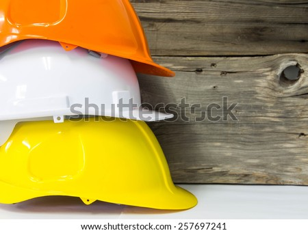 Orange safety hat on wood background - stock photo