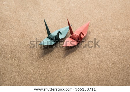 2 origami cranes on leather - stock photo