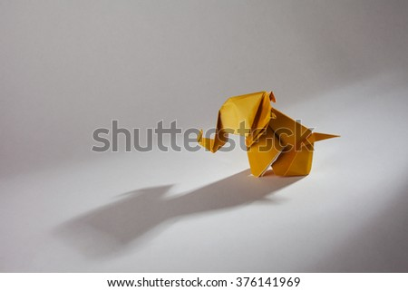 Origami elephant made of yellow paper isolated on white. - stock photo