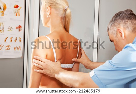 orthopedist make examination of the spine in his office - stock photo