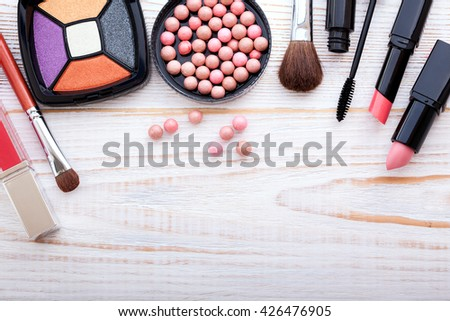 ?osmetics products on white. Cosmetics makeup artist objects: lipstick, eye shadows, powder, tools for make-up. Selective focus top view. - stock photo