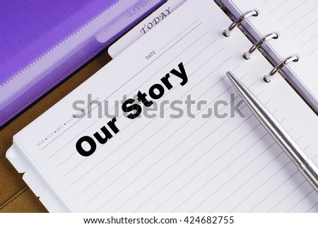 """Our Story"" text on notebook on a wooden table with open diary and pen - conceptual images"