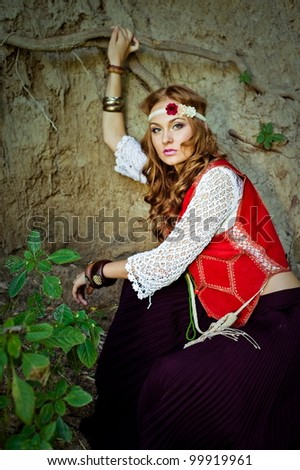 outdoor portrait of beautiful hippie girl sitting in woods - stock photo
