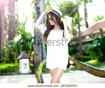 .Outdoor summer fashion portrait of beautiful elegant woman wearing luxury vintage hat and boho chic outfit, posing at windy sunny day at tropical beach, amazing view to the ocean. - stock photo