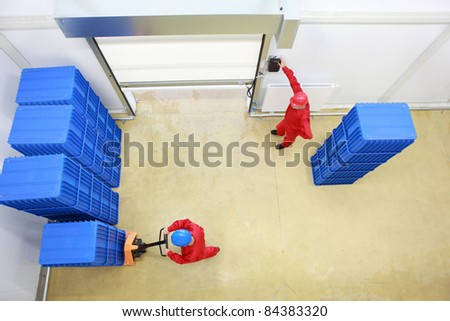 Overhead view of two workers. one is opening a gate another is loading plastic boxes  in small warehouse - stock photo