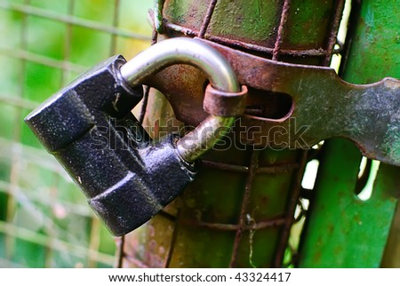 padlock  The closed old lock, hanging on a fence - stock photo