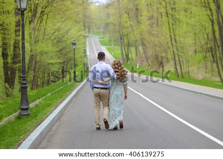 pair girl and the guy walk in the park tender love going back forest road spring green leaves bloom love - stock photo
