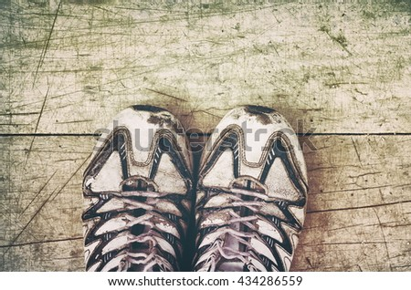pair of old worn sneakers on a wooden background, retro filter - stock photo