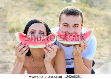 Pair on a picnic together bite a one piece of watermelon - stock photo