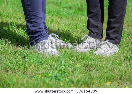 2 pairs of legs with white sneakers and jeans on the background of grass