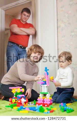 parents and child plays with meccano set in home - stock photo