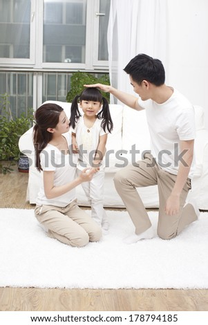Parents measuring height for daughter	 - stock photo