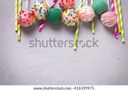 Party background. Colorful  bright cake pops and paper straws on  grey textured  background. Selective focus. Place for text. - stock photo