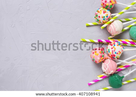Party background. Colorful cake pops and paper straws on  grey textured  background. Selective focus. Place for text. - stock photo