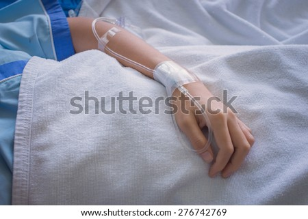 patient lady in hospital bed  with saline intravenous (iv) - stock photo