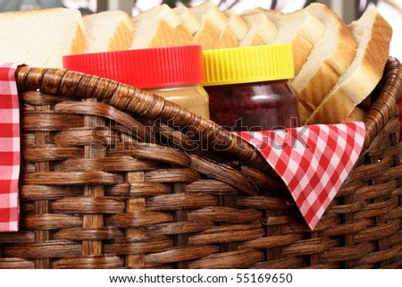 peanut butter and jelly sandwich ingredients on basket with jars and bread - stock photo