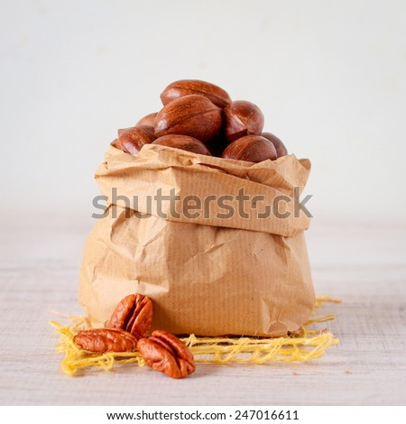 Pecan nuts in a paper bag on  wooden table - stock photo