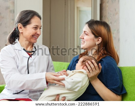 pediatrician doctor examining newborn baby - stock photo