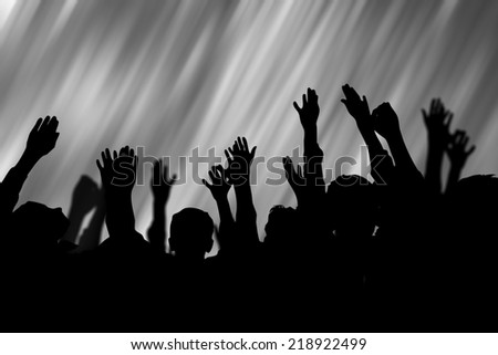 people rise hands in silhouette