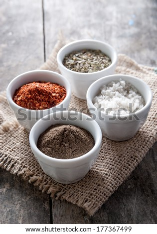 pepper, oregano and cooking salt in bowls on rustic wooden background - stock photo