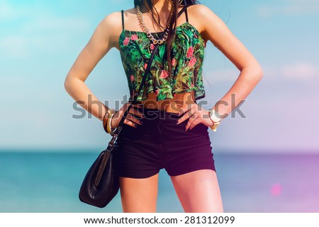 Perfect fit  girl  with  tan body  posing on the tropical  beach wearing bright colored top, hight shorts and stylish swag accessories . - stock photo