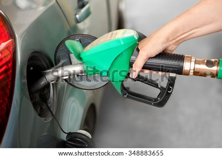 Person Refueling the Car at a Gas Station - stock photo
