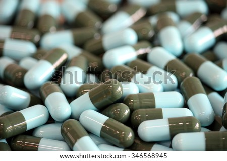 Pharmacy theme, Heap of blue green round capsule pills with medicine antibiotic. Shallow DOF - stock photo