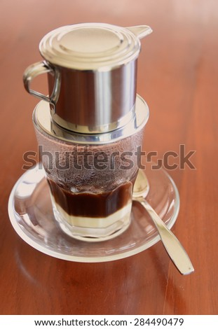 'Phin' traditional Vietnamese coffee maker, place on the top of glass, add ground coffee then pour hot water and wait until the coffee dripping into the glass with condensed milk at the bottom - stock photo