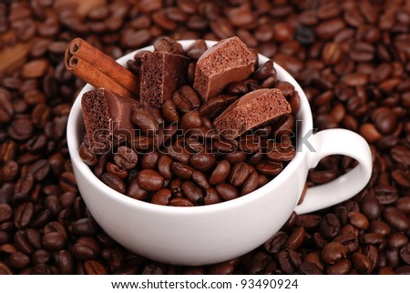 photo of chocolate, coffee beans and cinnamon in a coffee cup/White cup with coffee beans