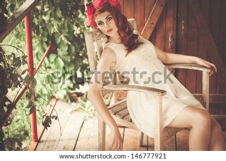 photo of the beautiful and sexy woman relax in village, seating in the armchair - stock photo