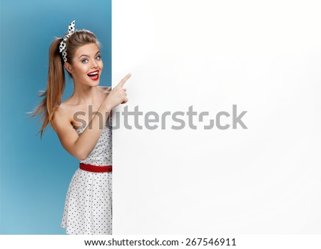 / photo set of young AmericanExcited woman showing empty blank banner with copy space for text pin-up model on blue background with space for text - stock photo