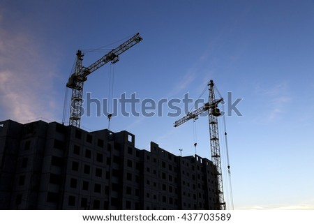 photographed close-up construction cranes during construction of a new multi-storey residential building - stock photo