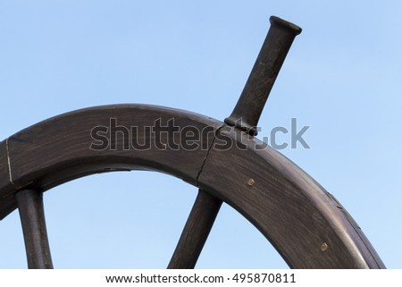photographed close-up part of the wheel of a large ship on a background of blue sky