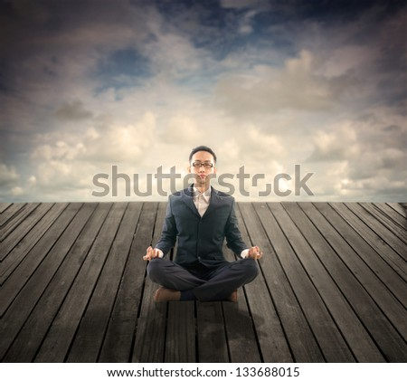 photos of business man relaxation on outdoor wood plank platform , lotus yoga stance - stock photo