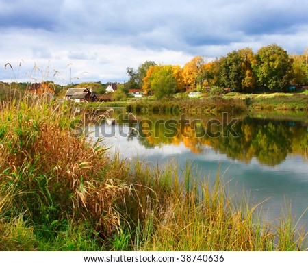 Picturesque autumn landscape of river and bright trees and bushes - stock photo