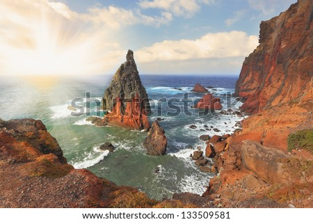 Picturesque colorful cliffs and islands.  The eastern tip of the island of Madeira.Madeira. Shining rays of the sun reflected in the water - stock photo