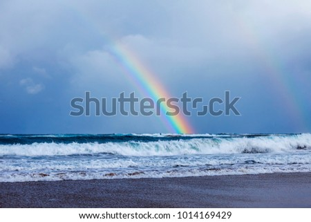 Picturesque waves wash the sandy beach on the seashore during a surf. A rainbow on the horizon