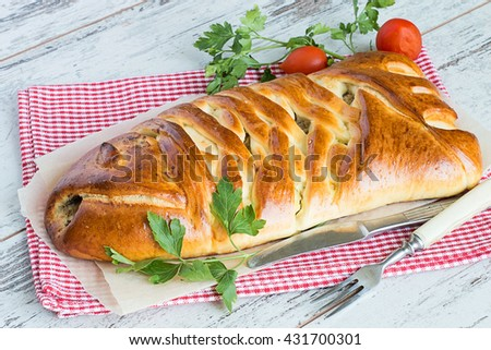 Pie with a fish on a napkin on a light wooden background.
