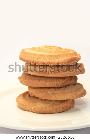 5 piece of sweet shortbread stacked on a cream china plate with a neutral background - stock photo