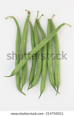 7 pieces of green beans isolated on white as 7 days of diet.