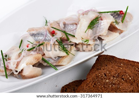 Pieces of salt fillet herring on a white plate and brown bread.