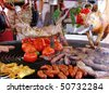 pig, meat and vegetables in course of barbecue preparation at spring fair in barcelona, spain - stock photo