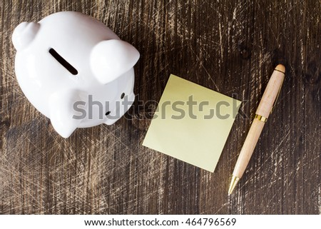 Piggy bank,sticky note and pen on wooden background, top view