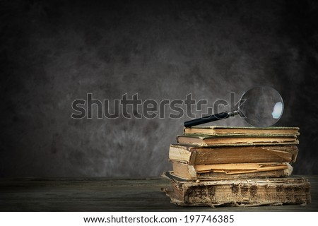 Pile of old antique and yellowed books with a magnifying glass - stock photo