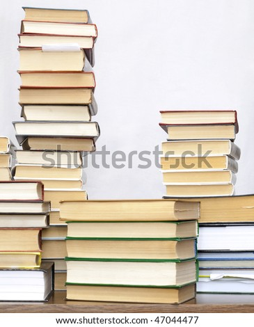 pile of old books on a wooden table on light background