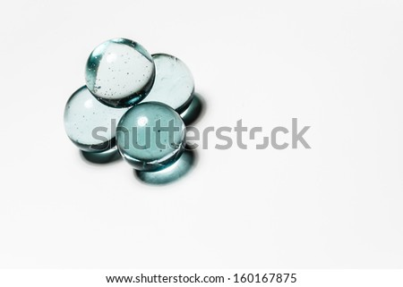 4 piled glass marbles - stock photo