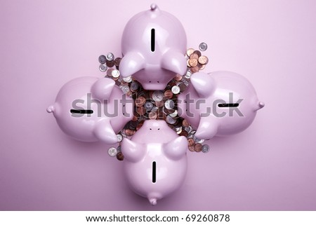 4 pink piggy banks and a pile of coins shot on pink background - stock photo