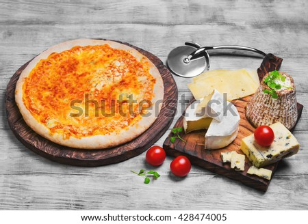4 Pizza four cheese, pizza ingredients for the four different types of cheese, goat cheese, lettuce, cherry tomatoes and a knife on a light wooden background - stock photo