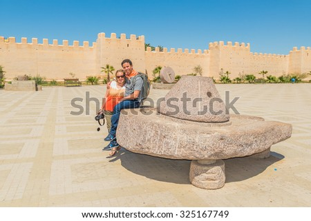 """""""Place 20 Aout"""" in Taroudant, Morocco - tourists posing on vintage quern - stock photo"""
