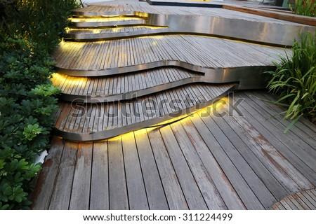 plank wood stair outdoor in flower garden ,Wood pathway in the garden, ground floor in yard - stock photo